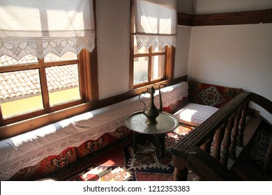 A traditional sofa covered by rugs and lace by the window, in Safranbolu Turkey.