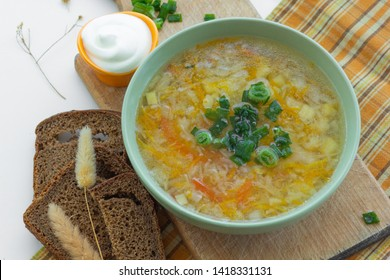 Traditional soup of Russia Shchi with green onion served with sour cream as garnish and rye bread