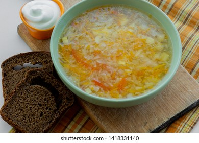 Traditional soup of Russia Shchi served with sour cream as garnish and rye bread