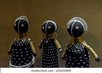 Traditional south african sangoma and ndebele black dolls decorated with golden rings and white beads