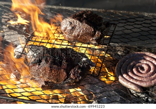 Traditional South African sausage called boerewors or just simply wors being grilled on a traditional braai along with sirloin steak.
