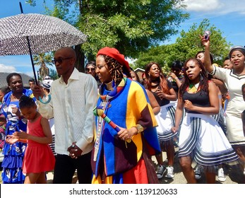 Traditional South African Wedding Between, Xhosa and Ndebele - Johannesburg, South Africa, 29 October 2017. Bride and groom followed by singers.