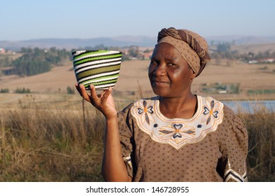 Traditional South African Zulu woman basket sales woman selling colourful ethnic baskets made from recycled wire