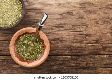 Traditional South American Yerba Mate tea in wooden mate cup with bombilla metal straw serving as a sieve, photographed overhead (Selective Focus, Focus on the top of the tea in the cup)