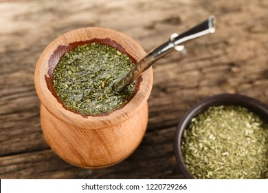 Traditional South American Yerba Mate tea in wooden mate cup with bombilla metal straw serving as a sieve, photographed on rustic wood (Selective Focus, Focus one third into the tea)
