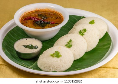 A traditional south Indian breakfast of fresh steamed Indian Idly (Idli / rice cake) served with coconut chutney, green coriander chutney and sambar