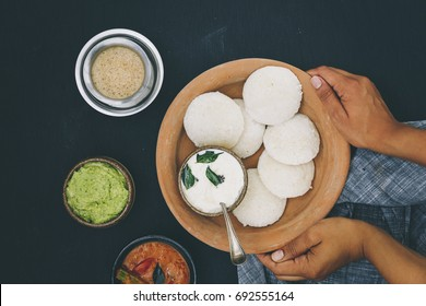 A traditional south Indian breakfast of fresh steamed Indian Idly (Idli / rice cake) served with coconut chutney, green coriander chutney, sambar and filter coffee