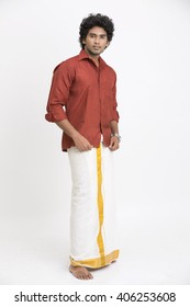 Traditional south Indian young man posing on white.