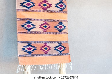 Traditional southwestern rug on display by adobe house wall, Taos, New Mexico, USA