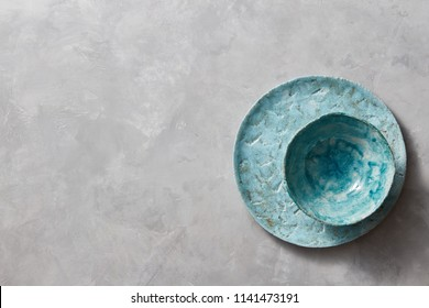 Traditional souvenir clay handmade colorful plate and bowl on a gray concrete background with place under text. Flat lay