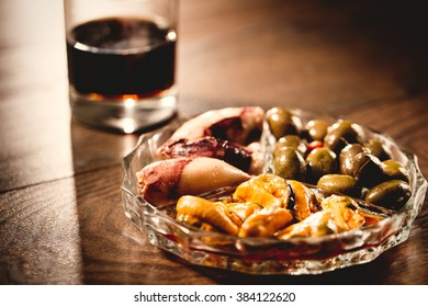 Traditional spanish appetizer with vermouth drink, canned food anc chips.
