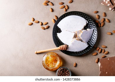 Traditional Spanish candy turron nougat with nuts served with honey, almonds and chocolate over brown texture background. Top view, flat lay