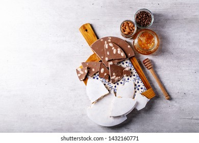 Traditional Spanish candy turron nougat with nuts served with honey, almonds and chocolate over white texture background. Top view, flat lay