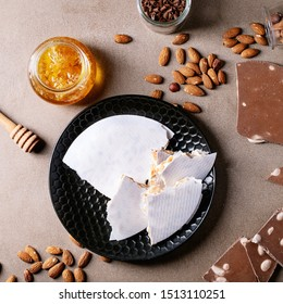 Traditional Spanish candy turron nougat with nuts served with honey, almonds and chocolate over brown texture background. Top view, flat lay. Square image