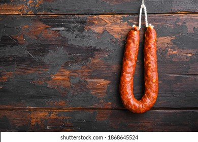 Traditional spanish chorizo sausage on wooden surface with space for text - Shutterstock ID 1868645524