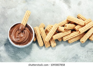 Traditional Spanish dessert churros with sugar and chocolate.