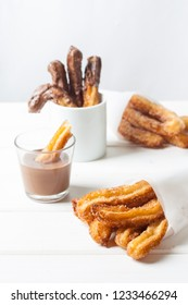 Traditional Spanish dessert churros with sugar and chocolate souce.