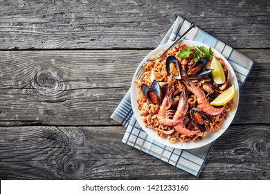 Traditional Spanish Fideua, a noodle Paella with seafood - king prawns, white fish meat, calamari, mussels served on a white plate on a wooden table with a fork, view from above, close-up, flatlay,
