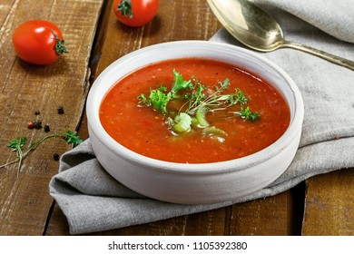 Traditional Spanish gazpacho on a rustic table. Delicious vegan cold tomato soup.
