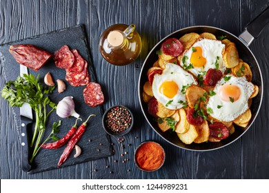 Traditional spanish huevos rotos - fried eggs with potatoes, pork sausages chorizo in a skillet on a black wooden table with ingredients, horizontal view from above, flat lay