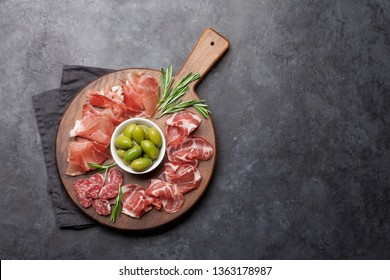 Traditional spanish jamon, prosciutto crudo, italian salami, parma ham. Antipasto plate and olives. Top view with copy space for your text