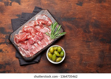 Traditional spanish jamon, prosciutto crudo, italian salami, parma ham. Antipasto plate and olives. Top view flat lay. With copy space