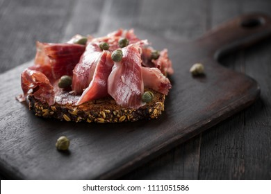 Traditional Spanish Jamon Serrano ham, Prosciutto Crudo, Parma ham, Italian antipasto, served on toasted bread.