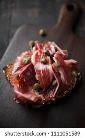 Traditional Spanish Jamon Serrano ham, Prosciutto Crudo, Parma ham, Italian antipasto, served on toasted bread.