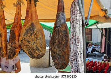 Traditional spanish legs ham and red wine on food market