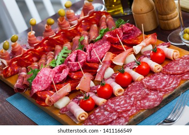 Traditional Spanish meat platter - sliced dry-cured jamon, bacon and sausages on wooden serving plate with olives, tomatoes and greens