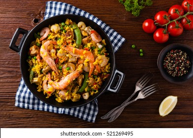 Traditional Spanish paella with seafood and chicken. Prepared in wook. Top view.