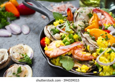 Traditional Spanish paella with seafood and vegetables in the vintage pan