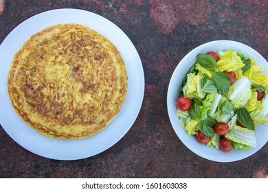 Traditional Spanish potatoes tortilla omelette with a salad bowl on a rusty table delicious food tapa tapas eat eating healthy