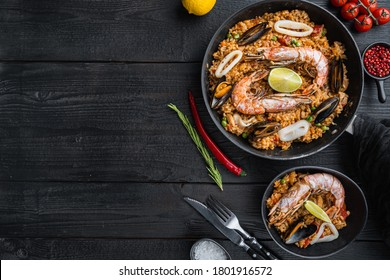 Traditional spanish seafood paella in pan and bowl with rice, peas, shrimps, mussels and squid on black wooden planks, top view with space for text