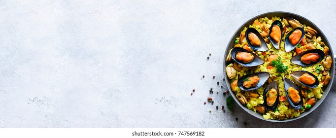 Traditional spanish seafood paella in pan rice, peas, shrimps, mussels, squid on light grey concrete background. Top view, copyspace