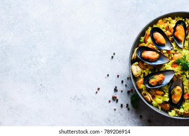 Traditional spanish seafood paella in pan rice, peas, shrimps, mussels, squid on light grey concrete background. Top view, copyspace. Square crop