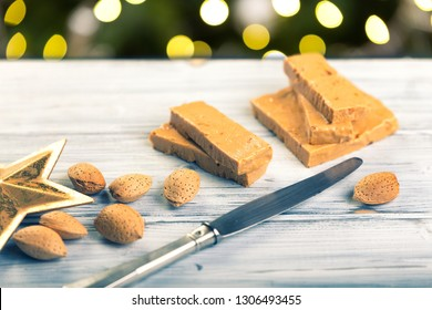 Turrón is a traditional Spanish sweets. Decorations of almonds and beautiful bokeh.