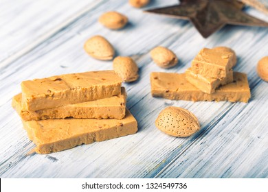 Turrón is a traditional Spanish sweets. Decorations of almonds on wooden table.