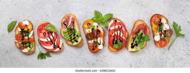 Traditional spanish tapas with tomatoes, mozzarella cheese, avocado and prosciutto on stone background. Flat lay. Top view