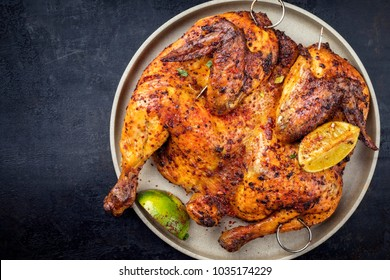 Traditional spatchcocked barbecue chicken al mattone with lemon slices as top view on a plate with copy space left