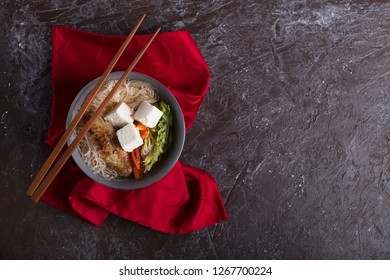 Traditional spicy asian soup with tofu cheese and noodles. This dish usually contains bouillon and vegetables. Dark brown background