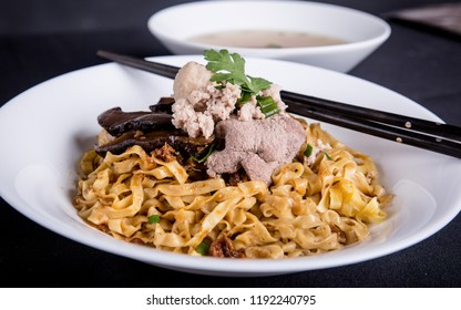Traditional spicy dry noodles served with mushrooms and pork. Bak Chor Mee from Singapore.