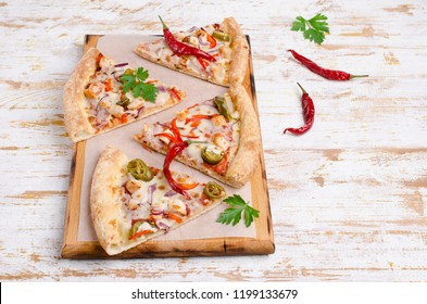 Traditional spicy pizza with meat and vegetables on wooden background. Selective focus.