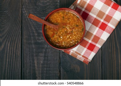 traditional spicy red lentil soup on the wooden background top view close-up