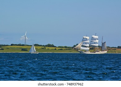 Traditional square-rigged tall ship and modern two-masted yacht at sea in front of a green seashore with fields and wind power station