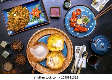 Traditional Sri Lankan kottu roti, hoppers cake, chicken spicy tikka boti in wooden background