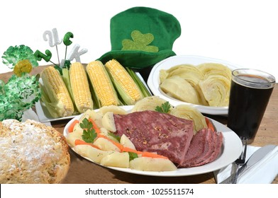 Traditional St. Patrick's day meal of corned beef, cabbage, potatoes, carrots, sweet corn, soda bread, along with a pint of dark Guiness beer perfect for traditional Irish celebration in March.