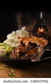 Traditional steak and ale pie with creamed potatoes and steamed leeks with thyme herb seasoning. Shot in a rustic, public house setting, with generous accommodation for copy space.