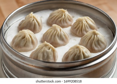 Traditional steamed dumplings in a silver dish ready to eat. Chinese food at its finest. close up of delicious food