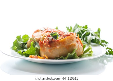 Traditional stewed manti in tomato sauce on a white background